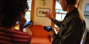 Energy Auditor showing a customer a potential problem area of their home, using thermal imaging.